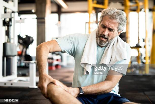 mature man having a strong knee pain in the gym. - knee stock pictures, royalty-free photos & images