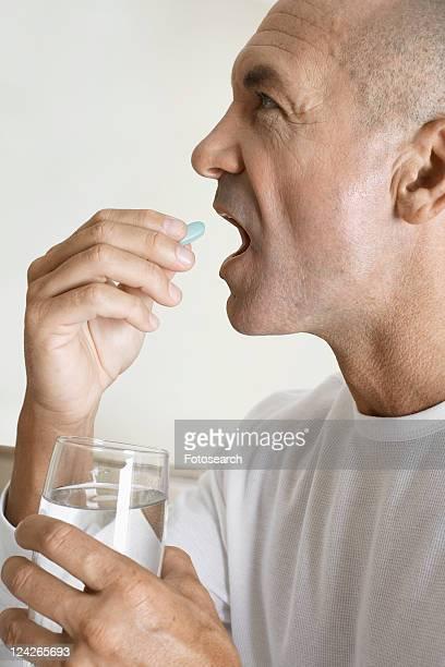 Mature man having a vitamin pill