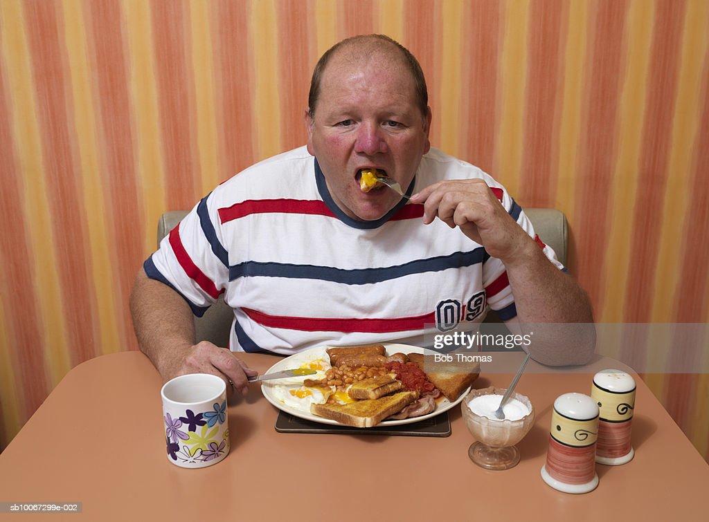 Mature man having breakfast at cafe, portrait : Stock Photo