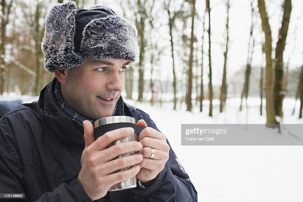 Mature man having hot drink outside in winter : Stock Photo