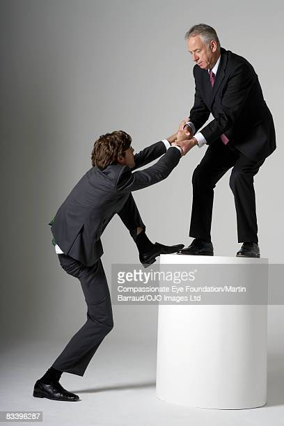 mature man helping a young man climb up - cef do not delete stock pictures, royalty-free photos & images