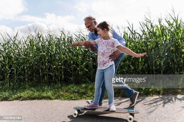 mature man helping little girl to learn skateboarding - mithilfe stock-fotos und bilder