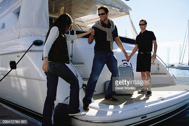 Mature man helping mature woman onto yacht in marina, smiling