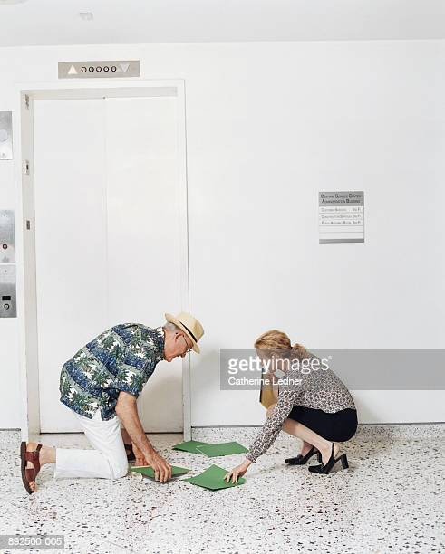 Mature man helping woman pick up files from floor