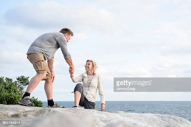 Mature man helping woman up onto rocks