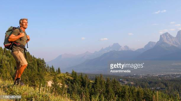 mature man hikes along mountain ridge at sunrise - early retirement stock pictures, royalty-free photos & images