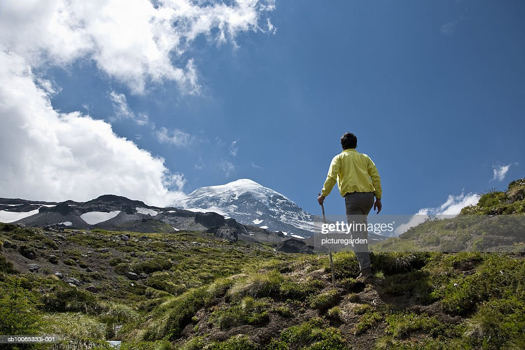 Mature man hiking on hill, snowcapped mountains in background, rear view : Foto stock