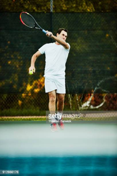 Mature man hitting forehand while playing early morning tennis match
