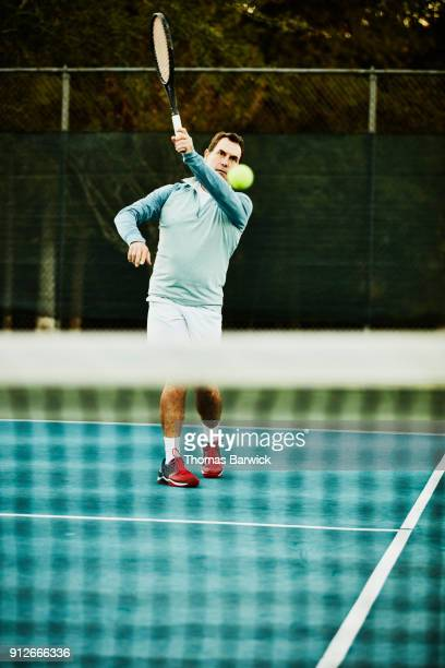 Mature man hitting forehand while warming up for early morning tennis match