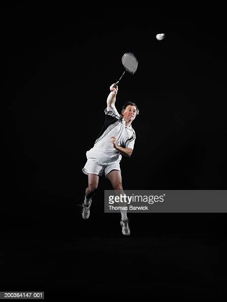 mature man hitting shuttlecock with badminton racket - スポーツ バドミントン ストックフォトと画像