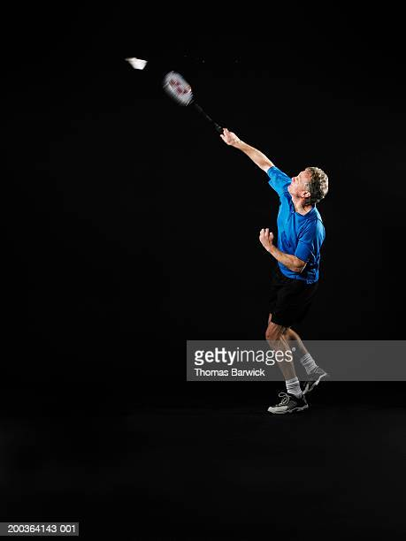 Mature man hitting shuttlecock with badminton racket, side view