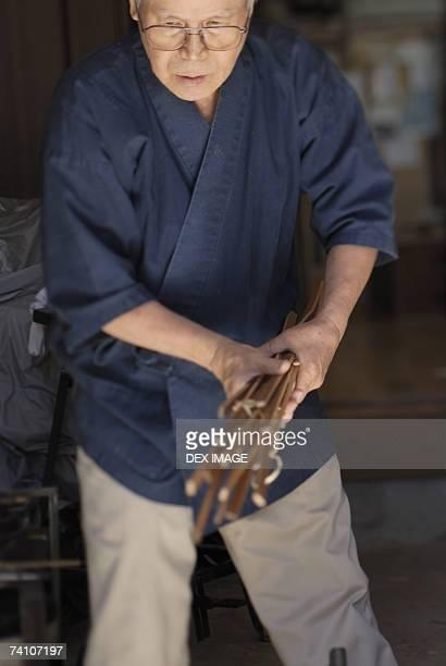 Mature man holding a bundle of wooden sticks