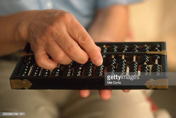 mature man holding abacus, mid section (focus on hand and abacus) - abaco imagens e fotografias de stock