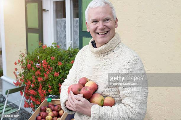 Mature man holding apples in his hands in front of wholefood shop and smiling, Bavaria, Germany