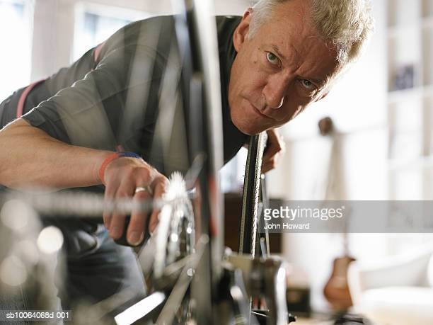 Mature man holding bicycle pedal, looking at wheel