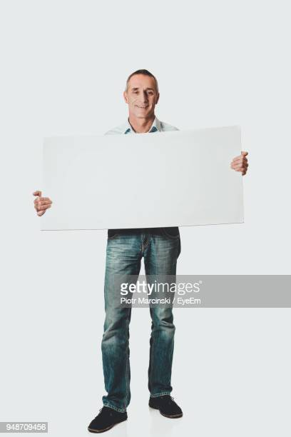 Mature Man Holding Blank Placard Against White Background