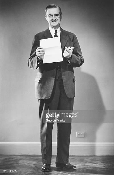 Mature man holding blank sheet of paper posing in studio (B&W), portrait