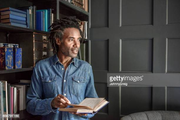 mature man holding book and looking away in panelled library - man holding book stock pictures, royalty-free photos & images