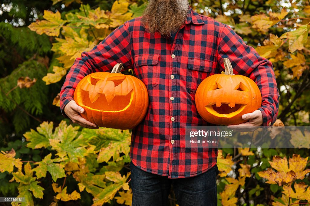 Mature man holding carved pumpkins : Stock Photo
