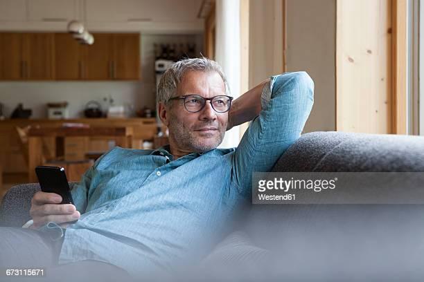 mature man holding cell phone sitting on couch - hände hinter dem kopf stock-fotos und bilder