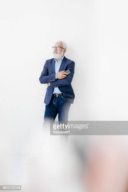 mature man holding cell phone standing at a wall - focus op achtergrond stockfoto's en -beelden