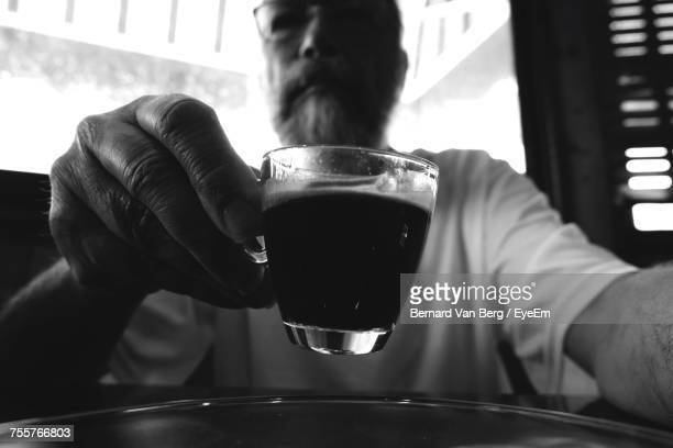 Mature Man Holding Coffee Cup At Cafe