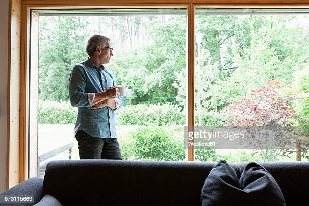 Mature man holding cup looking out of window