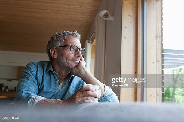 Mature man holding cup sitting on couch