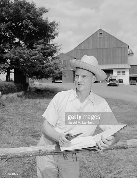 mature man holding diary and looking away - {{ contactusnotification.cta }} stockfoto's en -beelden