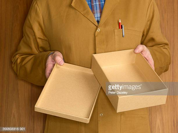 Mature man holding empty box, mid section