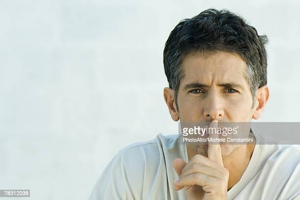 Mature man holding finger over lips, looking at camera, portrait