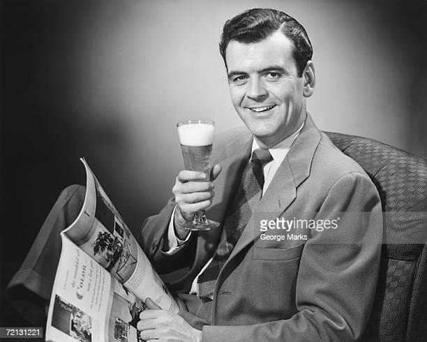Mature man holding glass of beer and magazine (B&W), portrait