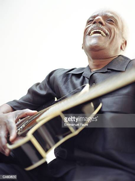 Mature man holding guitar and laughing