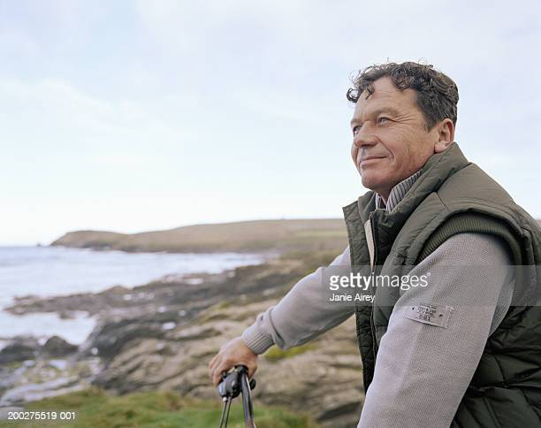 Mature man holding handle bar on bicycle, overlooking sea