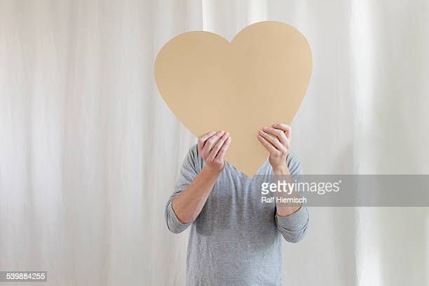 Mature man holding heart shape in front of face at home