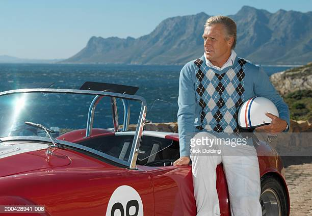Mature man holding helmet sitting on convertible racing car by coast