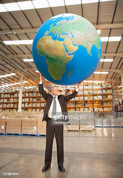 Mature man holding large blue ball on top