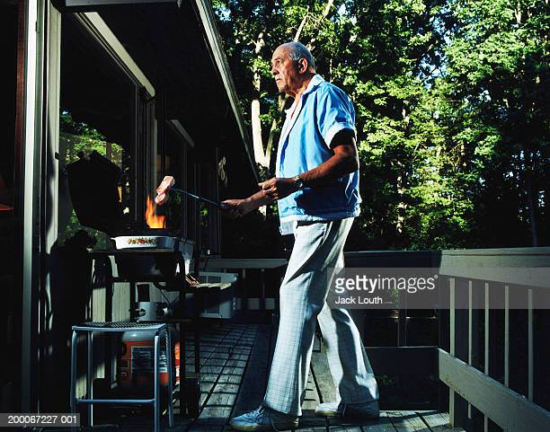Mature man holding meat over barbecue flame, side view