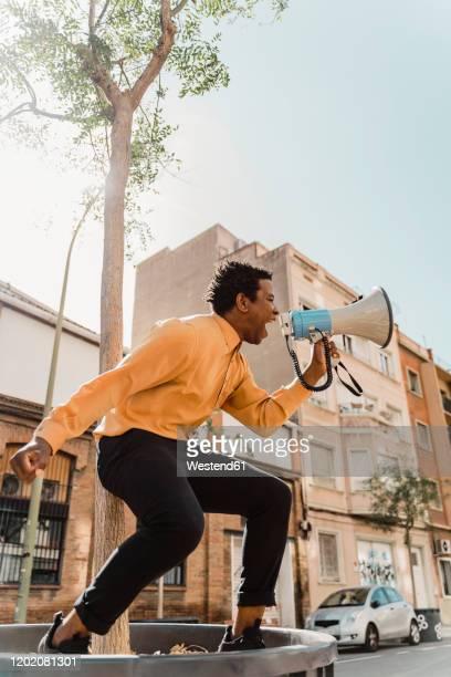 mature man holding megaphone and screaming - s'impliquer à fond photos et images de collection