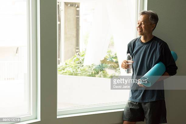 Mature man holding rolled up yoga mat and bottle of water looking out of window