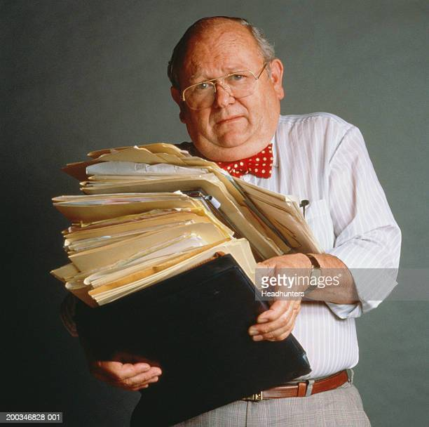 mature man holding stack of files - headhunters stock pictures, royalty-free photos & images