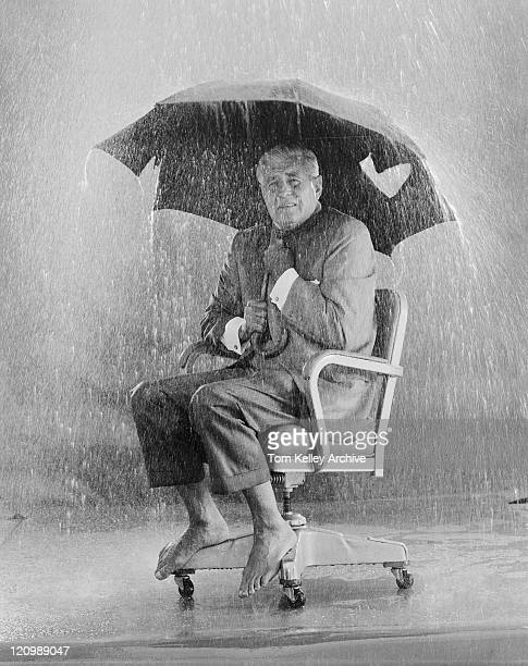 mature man holding torn umbrella in rain - inconvenience stock pictures, royalty-free photos & images