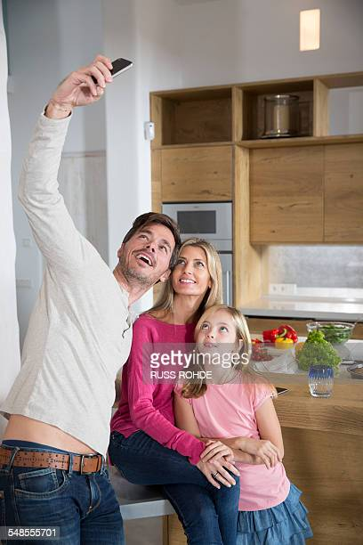 Mature man holding up smartphone for family selfie in dining room
