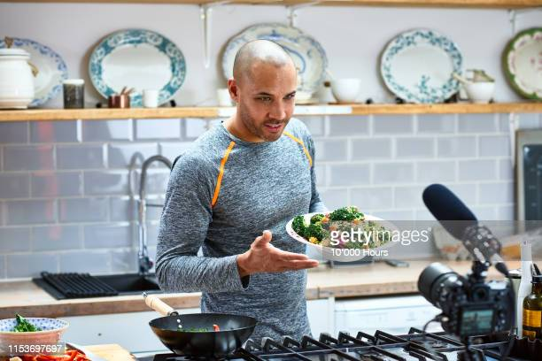 mature man holding vegetarian food and talking to video camera - vegetarianism stock pictures, royalty-free photos & images