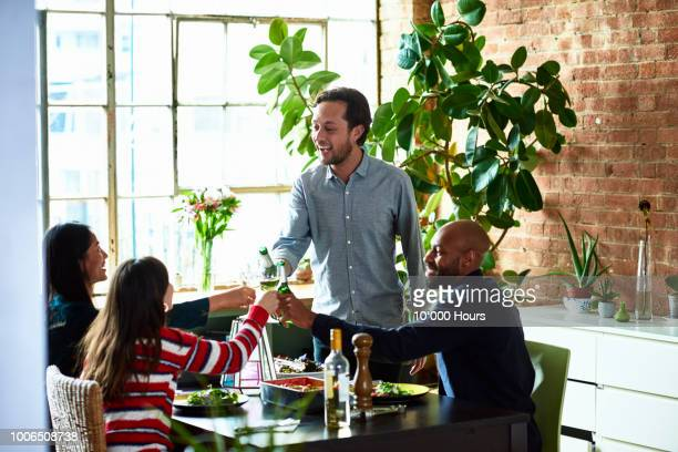 mature man hosting informal dinner party with friends and pouring drinks - party host stock pictures, royalty-free photos & images