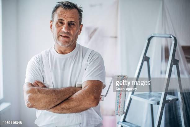 reife mann haus maler mit armen gekreuzt - maler stock-fotos und bilder