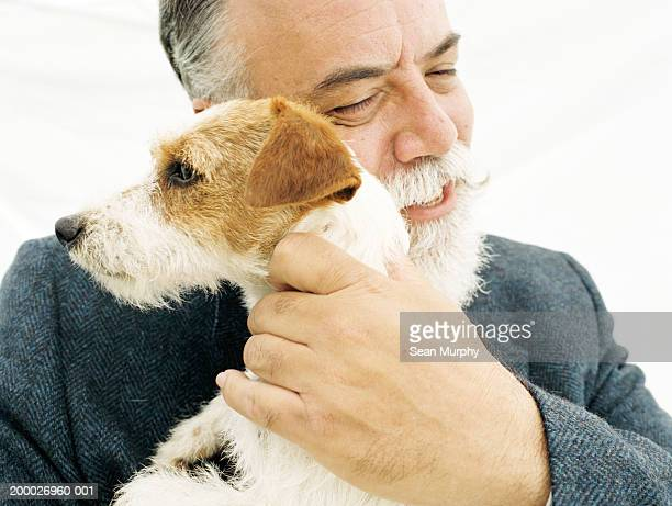 Mature man hugging Jack Russell Terrier