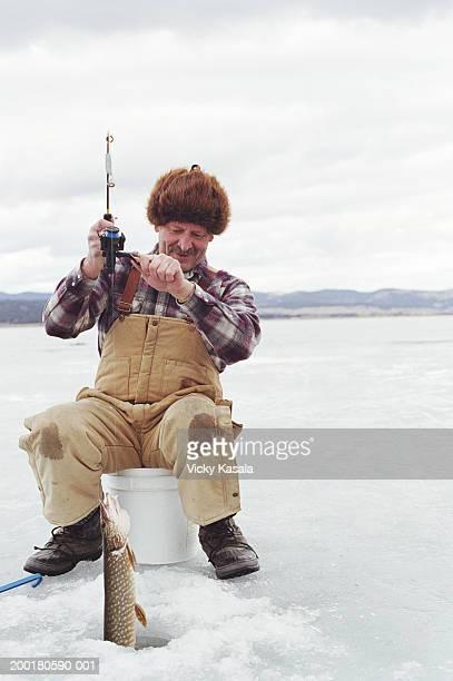 Mature man ice fishing on frozen lake