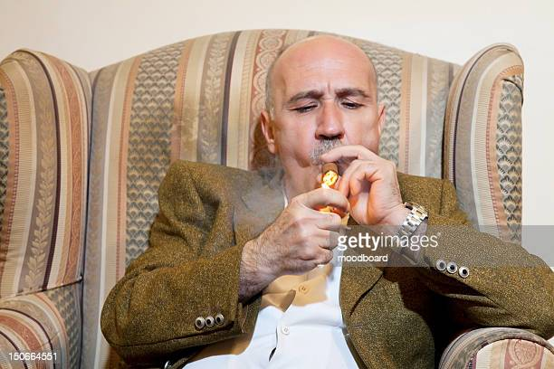 Mature man igniting cigar while sitting on armchair