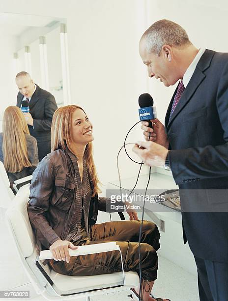 mature man in a suit holding a microphone and interviewing a pop musician in her dressing room - pop musician stock pictures, royalty-free photos & images